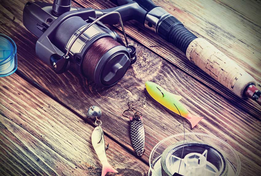 fishing reel, rod, and tackle on wooden bench